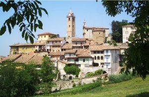 Paesaggio con prati verdi e borgo antico